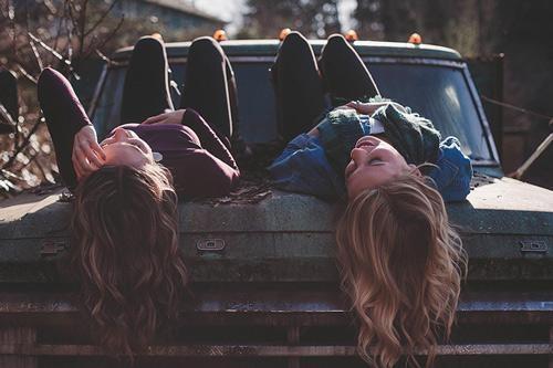 twee jonge vrouwen relaxen op een roestige oude auto